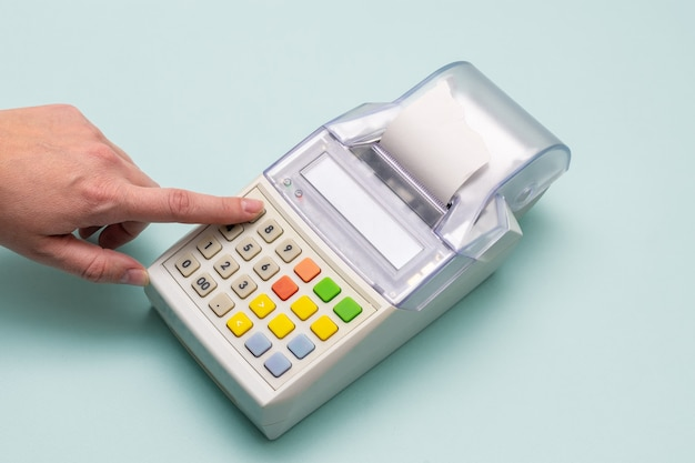 Close-up of a woman's hand pressing her finger in a cash register button