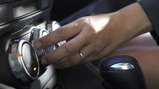 Close up woman's hand, she push start button and turn up or on air condition in modern car.