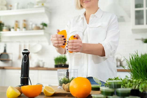 Close-up of a woman's hand squeezing orange juice to make a wheat juice smoothie. whitgrass, healthy food.