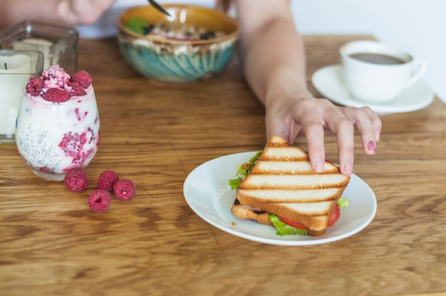 Close-up of woman's hand taking sandwich from ceramic plate on wooden table