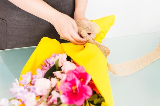 Primo piano della mano di una donna che lega il mazzo di fiori con il nastro
