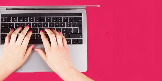 Close-up of woman's hand typing on laptop keypad over pink background