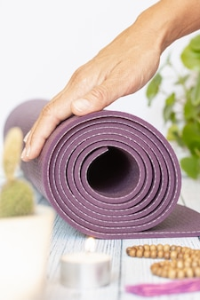 Close-up of a woman's hand unfolding a violet yoga mat, bad wood beads on white wood. essential accessories for practicing yoga and meditation.