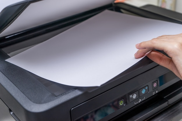 Close up woman's hand with working copier, printer