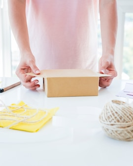 Close-up of a woman's hand wrapping the gift box on white table