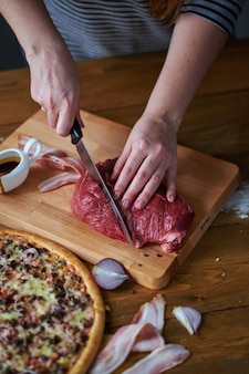 Close-up of woman's hands cut beef with knife. red onion, ham slices and pizza on table.