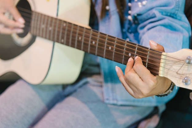 Close up woman's hands playing acoustic guitar.