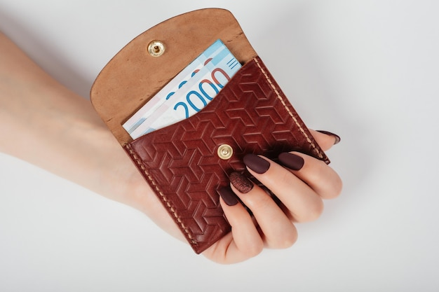 Close-up of a woman's hands putting banknote of thousands rubles in a purse.