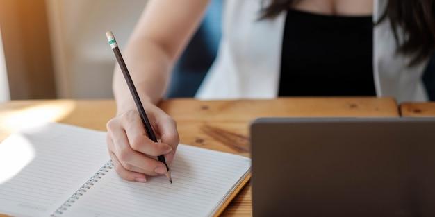 Закройте руки женщины с портативным компьютером, блокнотом и ручкой, делая заметки в деловом офисе