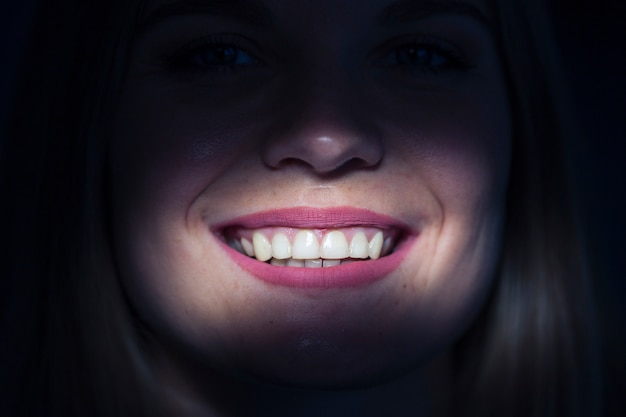 Close-up of a woman's illuminated teeth