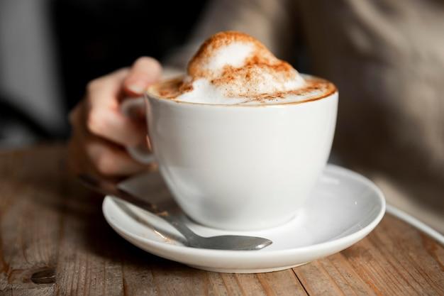 コーヒーの警官を提供するクローズアップの女性