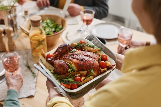 Close-up of woman serving roast chicken for dinner for her family in the dining room
