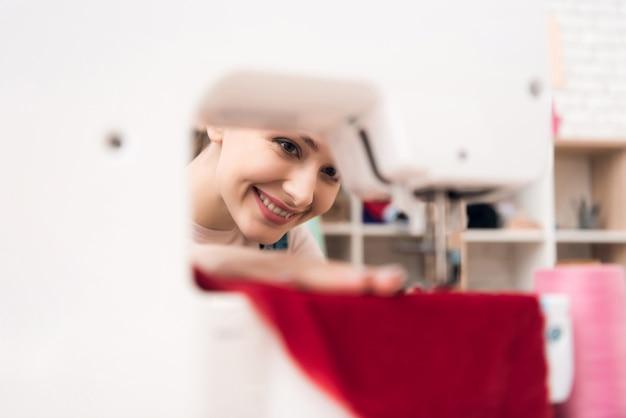 봉 제 기계에 여자 sews 옷을 닫습니다