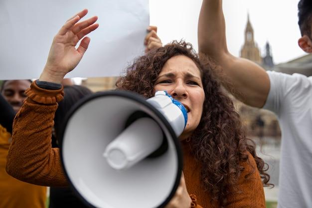 メガホンに向かって叫んでいる女性をクローズアップ
