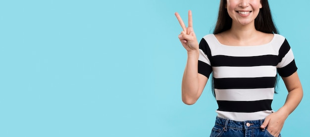 Close-up woman showing peace sign
