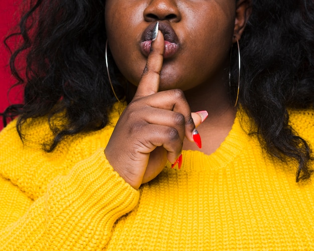 Close-up woman showing silence sign