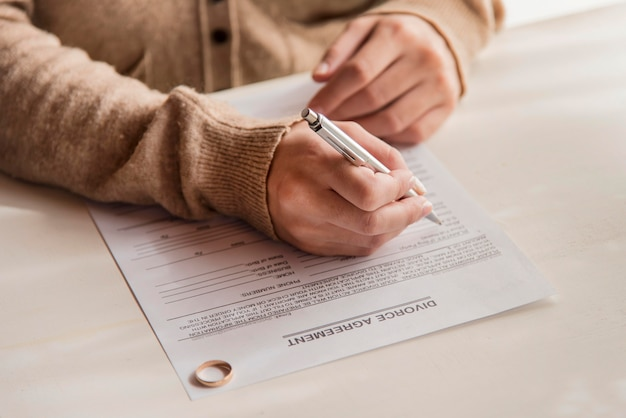 Close-up woman signing divorce agreement