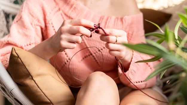 座ってかぎ針編みのクローズアップ女性