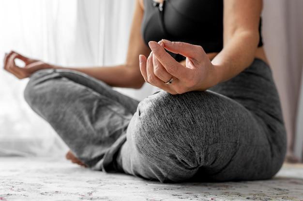 Крупным планом женщина сидит и медитирует
