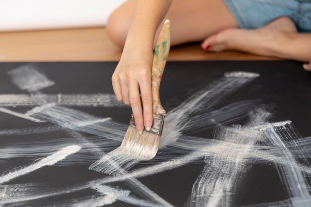 Крупным планом женщина сидит и рисует
