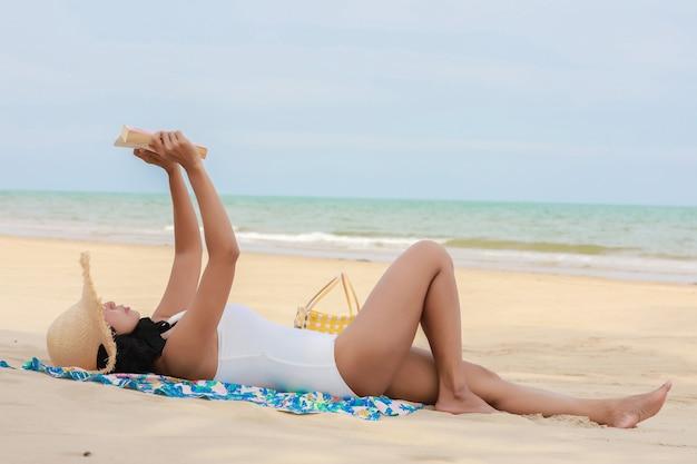 クローズアップ女性は本を読んで夏のビーチで日光浴をします。
