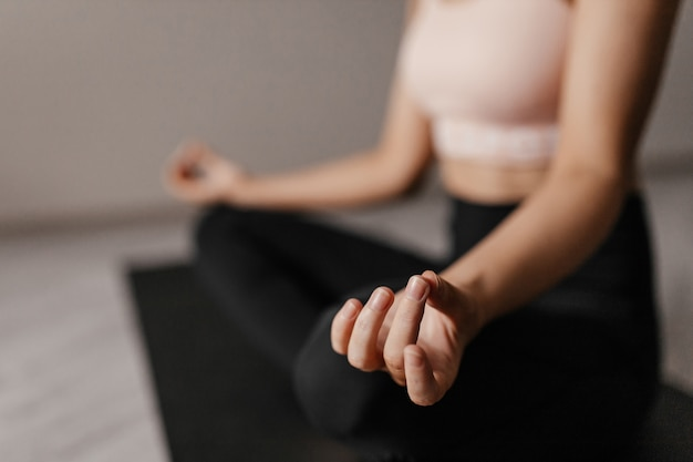 Close up on woman in sportswear practicing yoga
