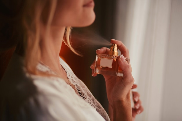 Close up woman spraying perfume