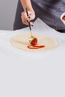 Close-up of a woman spreading the tomato sauce on pizza bread over the parchment paper