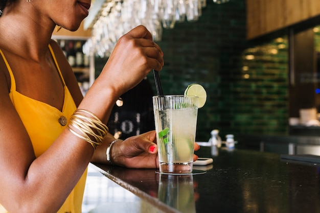 Close-up of woman stirring a mojito at bar counter