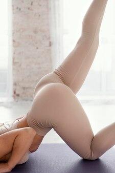 Женщина крупным планом, растягиваясь на коврике