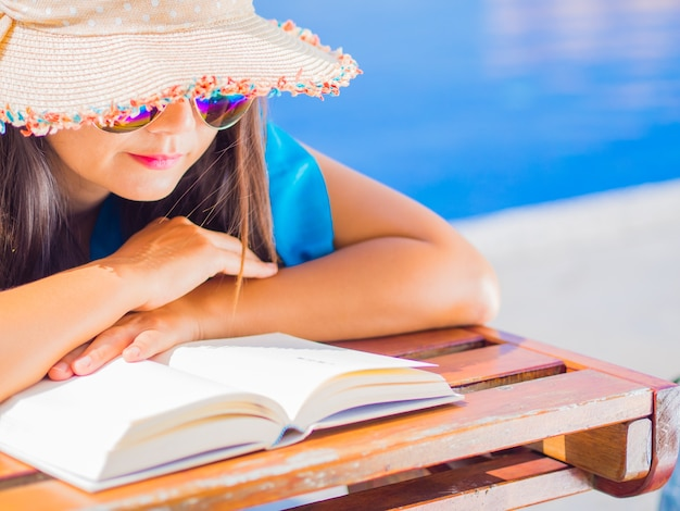 Close up woman in summer hat lying on deckchair and reading a book