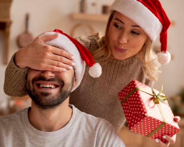 Крупным планом женщина удивляет мужчину с подарком