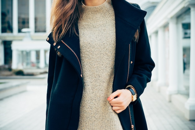 Close-up of a woman in a sweater, a coat, and a wristwatch