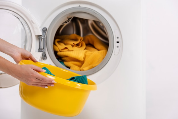 Close-up woman taking clothes out of washing machine
