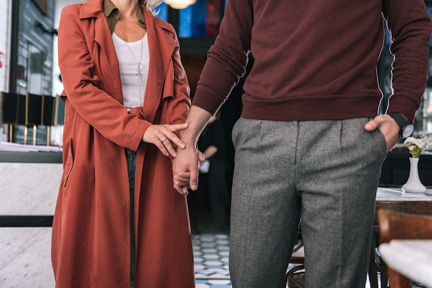 Close up of woman taking male hand while man putting hand in pocket