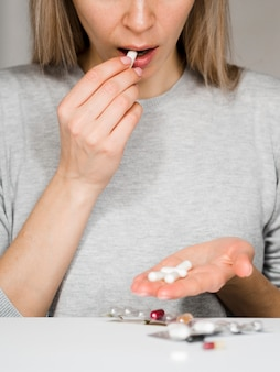 Close-up woman taking pill