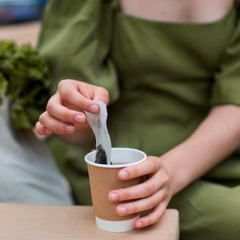 Крупным планом женщина берет чайный пакетик из чашки