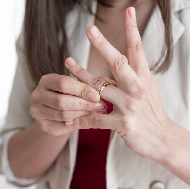 Close-up woman taking wedding ring off finger