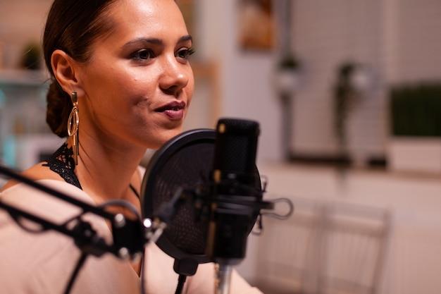 Primo piano di una donna che parla al microfono durante lo streaming. trasmissione online di produzione online in onda mostra host in streaming di contenuti live, registrazione di comunicazioni sui social media digitali