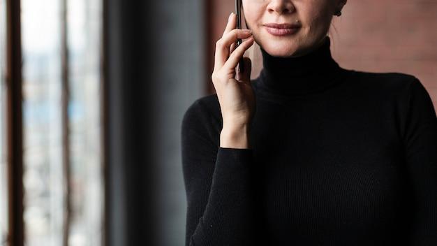 Donna del primo piano che parla sopra il telefono