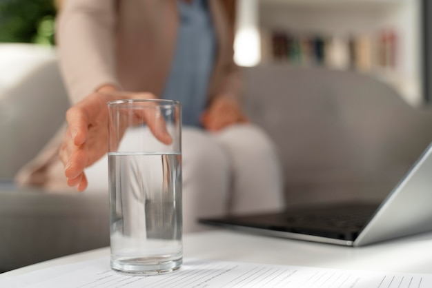 Close-up woman therapist reaching for glass of water