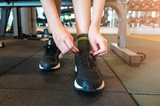 Close up woman tie up her shoe in gym