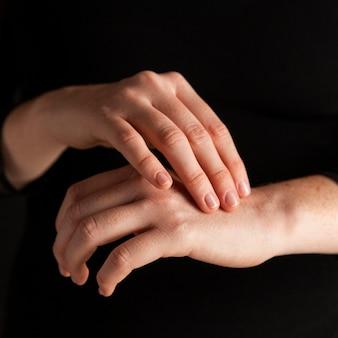 Donna del primo piano che tocca le mani