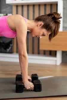 Тренировка женщины с гантелями крупным планом