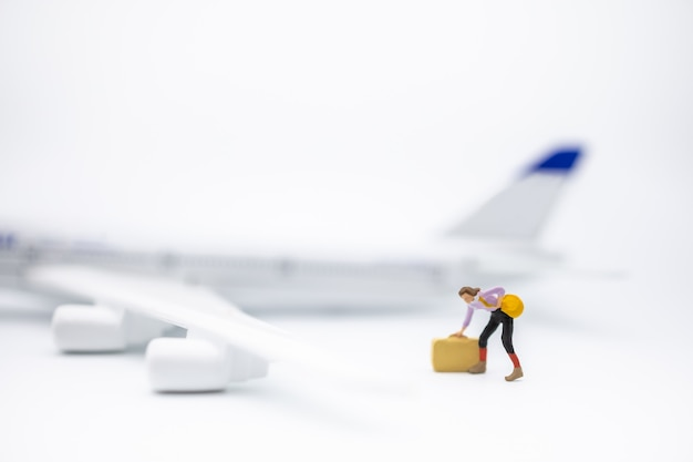 Close up of woman traveler miniature figure with baggage standing on white with mini toy airplane model.