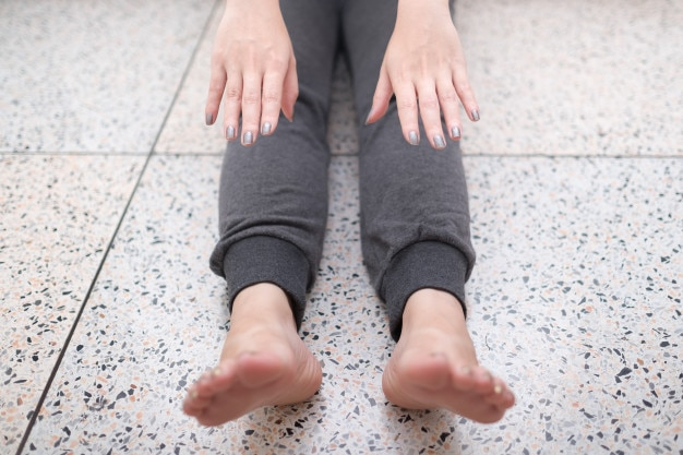 Close up woman try hard to stretching her tight leg on floor