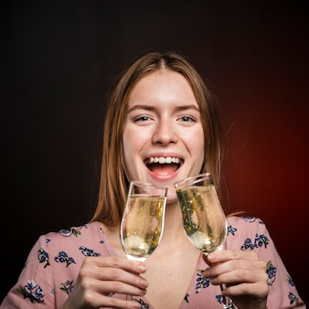 Close-up woman trying to drink champagne from two glasses