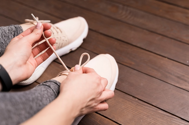 Close-up woman tying her shoe laces at the gym