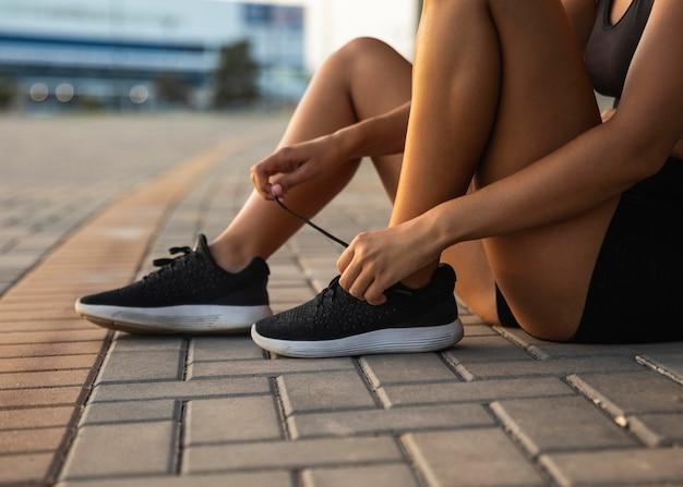 Donna del primo piano che lega i suoi lacci delle scarpe