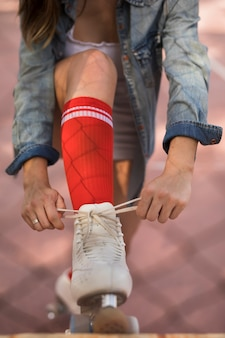 Close-up of a woman tying the lace of roller skater